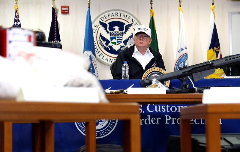 "FILE - In this Jan. 10, 2019, file photo, illegal drugs and weapons are displayed in the foreground as President Donald Trump speaks at a roundtable on immigration and border security at the U.S. Border Patrol McAllen Station in McAllen, Texas. In his demands that Congress set aside $5.7 billion for a border wall, President Donald Trump insists a physical barrier would stop heroin entering the U.S. from Mexico. But U.S. statistics, analysts and testimony at the trial of drug kingpin Joaquin ""El Chapo"" Guzman in New York show that most hard drugs entering the U.S. from Mexico come through land ports of entry staffed by agents, not open sections of the border. (AP Photo/Evan Vucci, File)"