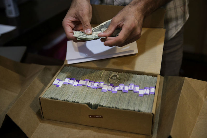 In this June 27, 2017 file photo, the proprietor of a medical marijuana dispensary prepares his monthly tax payment, over $40,000 in cash, at his Los Angeles store. Congress on Wednesday, Feb. 13, 2019, was urged to fully open the doors of the nation's banking system to the legal marijuana industry, a change that supporters say would reduce the risk of crime and resolve a litany of problems for pot companies from paying taxes to getting a loan. (AP Photo/Jae C. Hong, File)