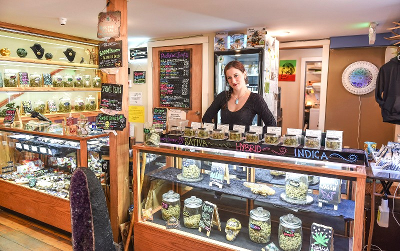 Kolbe Rose, the manager of Stoney Moose cannabis store, stands behind some of the stores display cases Wednesday, March 6, 2019, in Ketchikan, Alaska. Alaska has moved closer to becoming the first in the country with statewide rules allowing onsite use of marijuana at specially authorized stores. Eric Riemer is a co-owner of The Stoney Moose retail marijuana shop in Ketchikan, a community that is a summer tourist destination in southeast Alaska. He said his business, which is not in a stand-alone building, has had to revise its initial vision of an upstairs consumption area as the regulations took shape and is now looking at some type of outdoor area. (Hall Anderson/Ketchikan Daily News via AP)