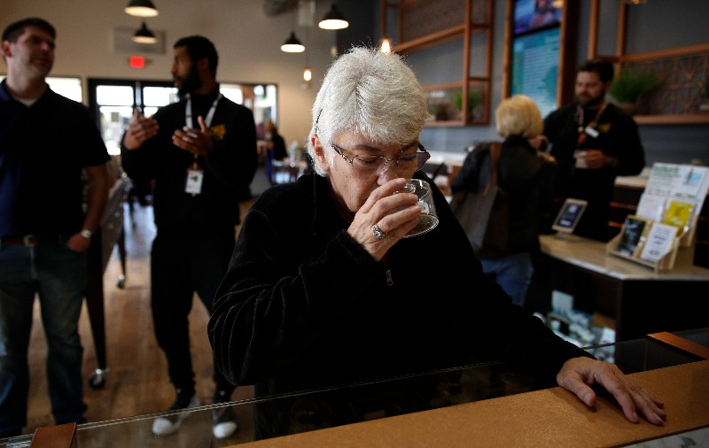 In this Feb. 19, 2019 photo, Sandy Sopher, 65, smells cannabis buds at Bud and Bloom cannabis dispensary in Santa Ana, Calif. As legal cannabis has spread to dozens of states, more Americans in their 70s and 80s are adding marijuana to the roster of senior activities such as golf and bingo. (AP Photo/Jae C. Hong)